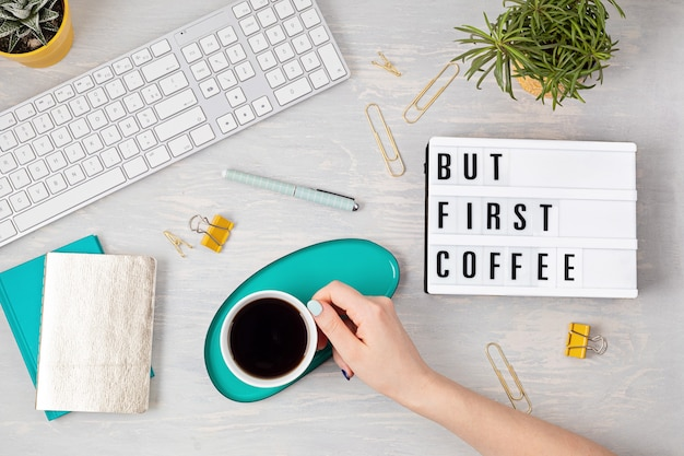 Flat lay with lightbox with text but first coffee and coffee cup in woman hand. social media, feminine blog, morning of workday concept. top view