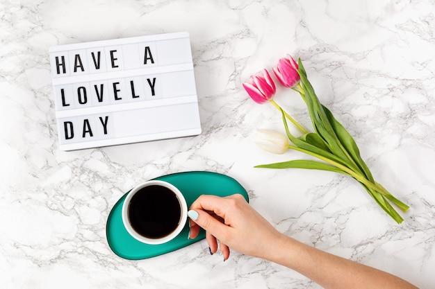 テキスト付きのライトボックス付きフラットレイ素敵な一日とコーヒーカップを女性の手に。ソーシャルメディア、モチベーションの引用、女性のブログ、就業日の朝のコンセプト