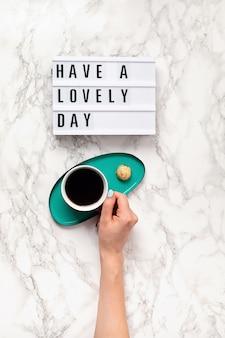 텍스트가있는 라이트 박스가있는 평면 배치 여자 손에 멋진 하루와 커피 잔을 보내십시오. 소셜 미디어, 동기 부여 인용문, 여성 블로그, 근무일의 아침 개념