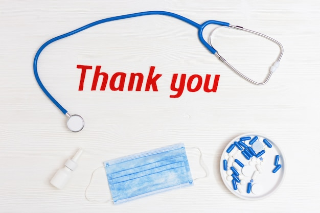 Плоская планировка с медицинским стетоскопом, таблетками, одноразовой маской и надписью. спасибо