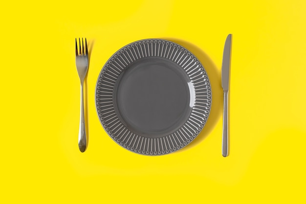 복사 공간이 유행 노란색 배경에 회색 접시와 칼을 모의와 평면 누워