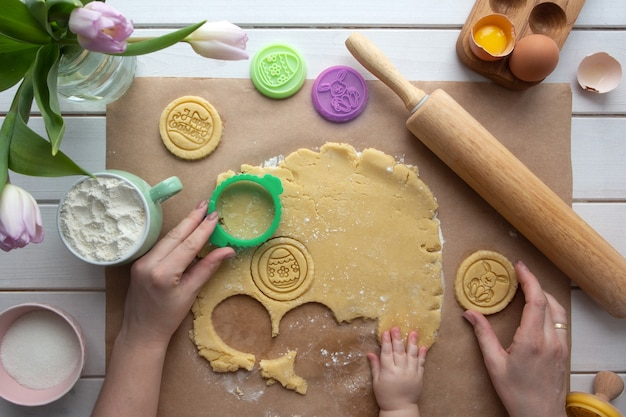 Плоский лежал с руками матери и ребенка, готовя пасхальное печенье