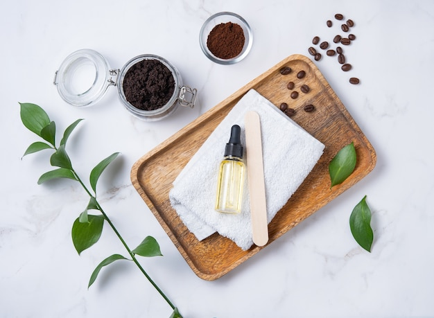 Flat lay with natural ingredients for home body coffee scrub with coffee beans, towel and olive oil in wooden plate on marble background.  body skin care. top  view and copy space