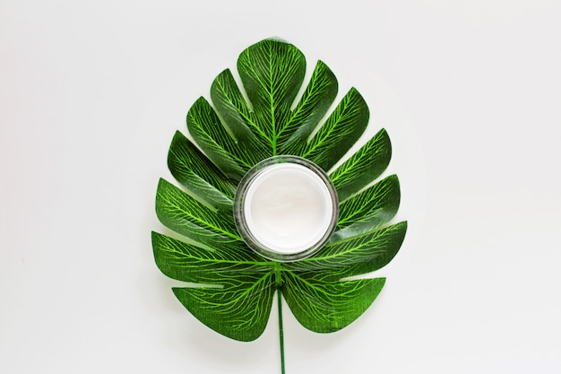 Flat lay with natural organic cosmetics: cream with green leaf. skincare, cosmetology, dermatology concept.