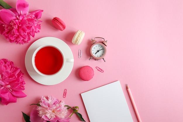 テーブルの上にメモ帳鉛筆目覚まし時計牡丹の花とお茶とマカロンのカップとフラットレイ