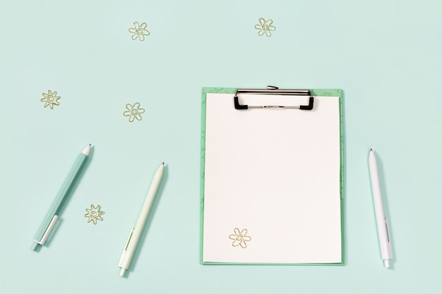Плоская планировка с канцелярскими принадлежностями, бумажным планшетом с зажимом, ручками, линейкой и металлическими скрепками