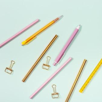 사무용품, 분홍색 및 황금색 색연필, 펜 및 금속 종이 클립이있는 평면 배치.