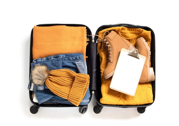 Flat lay with open suitcase with casual clothes for autumn, winter vacations over white wall. winter holidays, travel, tourism, flight luggage concept. top view
