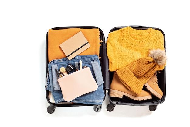 白い壁の上に秋、冬の休暇のためのカジュアルな服を着たオープンスーツケースでフラットレイ。冬の休日、旅行、観光、フライト荷物のコンセプト。上面図
