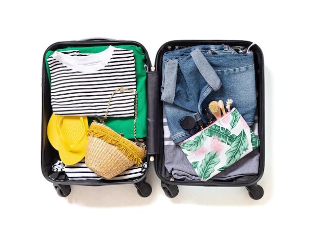 Квартира лежала с открытым чемоданом с повседневной одеждой для летних каникул над белой стеной. летние каникулы, путешествия, туризм, концепция багажа полета. вид сверху