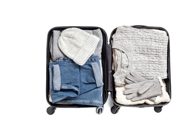 カジュアルな服装のオープンスーツケースとフラットレイ