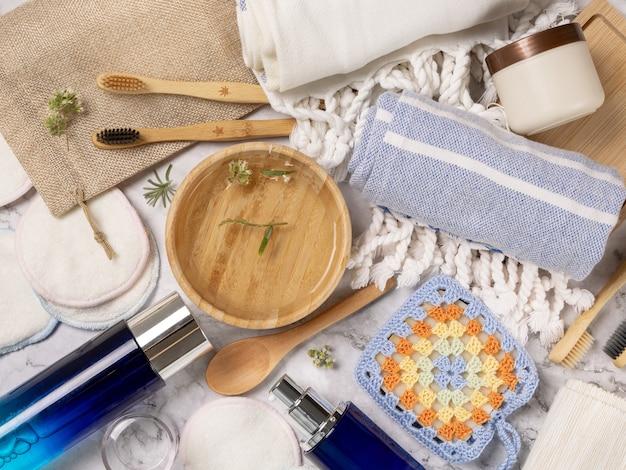 대리석 탁자에 있는 피부와 모발 관리를 위한 유기농 천연 화장품과 재사용할 수 있는 액세서리가 있는 평평한 평지. 목욕, 마사지 또는 스파 살롱을 위한 친환경 메이크업 및 미용 제품의 상위 뷰