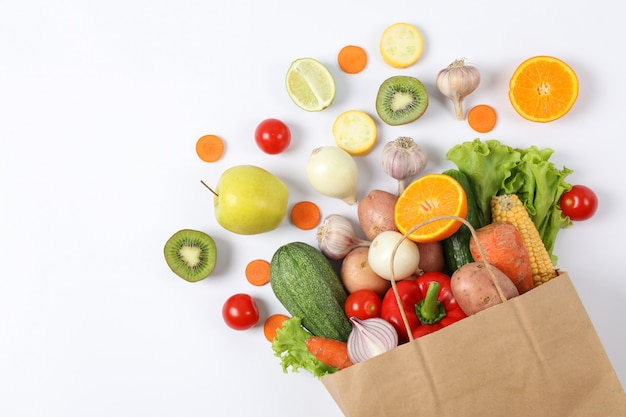 Flat lay with paper bag, vegetables and fruits on white