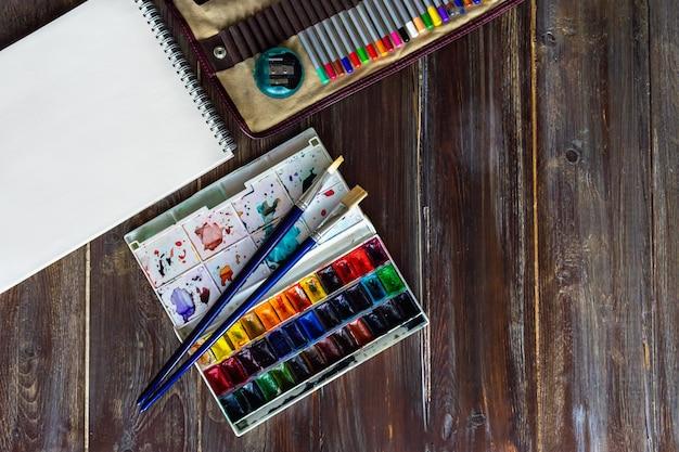 鉛筆、ブラシ、水彩絵の具、紙、クレヨンパステルチョークでフラットレイアウト