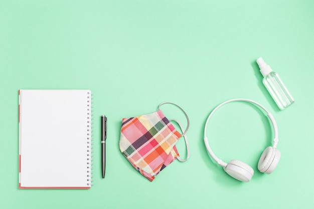Flat lay with personal protective equipments for students. face medical mask, hand sanitizer, notebook, pen, white headphones on neo mint colored paper background.