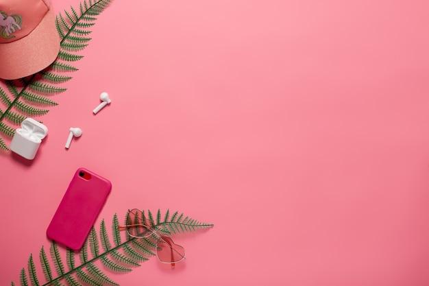 電話アクセサリーと野球帽を備えたフラットレイ。ピンクの孤立した背景フラットレイにコピースペースを持つ電話、野球帽、電話アクセサリー。