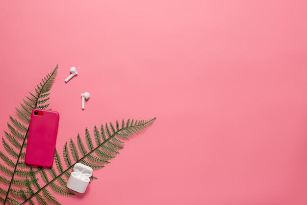 ピンクの孤立したバックにコピースペースのある電話アクセサリー電話と電話アクセサリーを備えたフラットレイ...