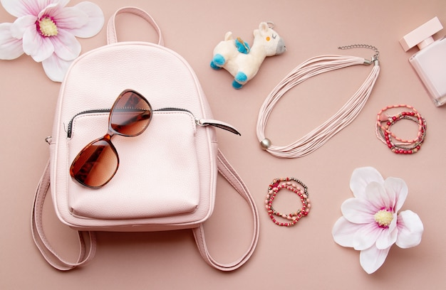 Flat lay with pink woman accessories  with backpack and woman hand holding the sunglasses. summer fashion trends, shopping concept