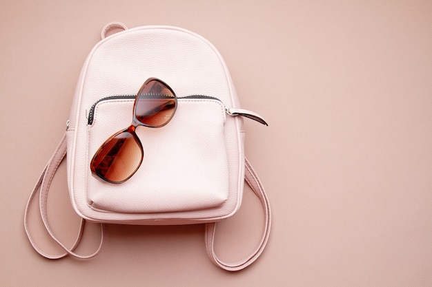 Flat lay with pink woman accessories  with backpack and woman hand holding the sunglasses. summer fashion trends, shopping idea
