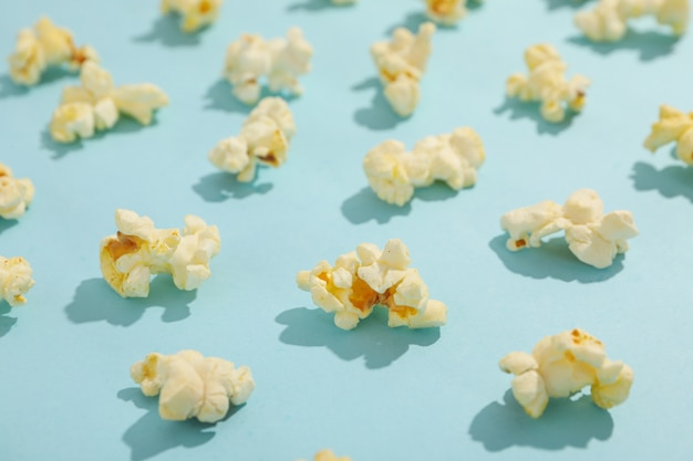 フラットは、青い空間にポップコーンを置きます。映画の食べ物