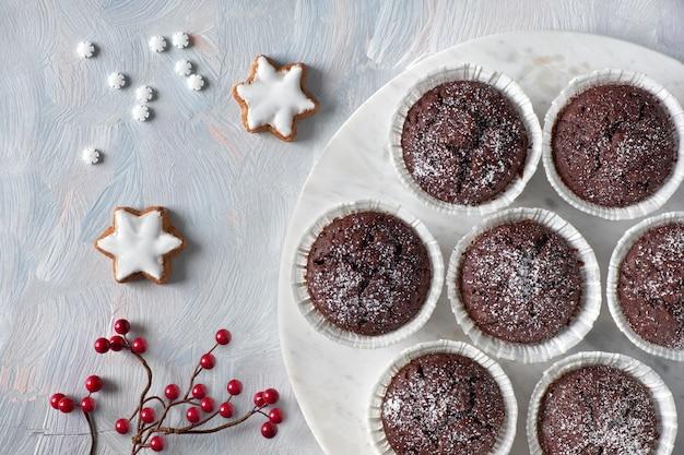 砂糖のアイシングで白い紙コップに赤いベリーの装飾とチョコレートのマフィンをフラットレイアウト