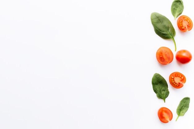Квартира лежала с красными помидорами черри и зелеными листьями шпината на белом фоне. концепция здорового питания