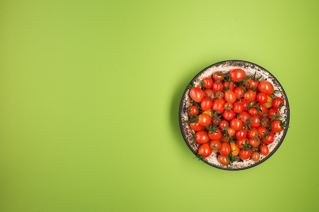 Flat lay with red tomatoes on green background.