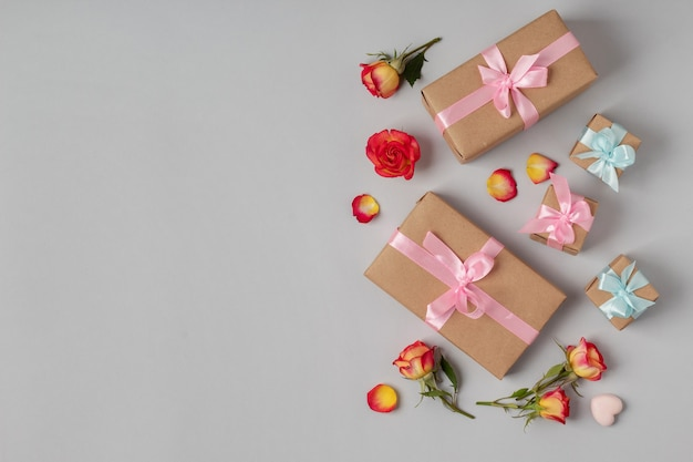 灰色の背景にバラの花とギフトボックスでフラットレイ。休日のお祝い