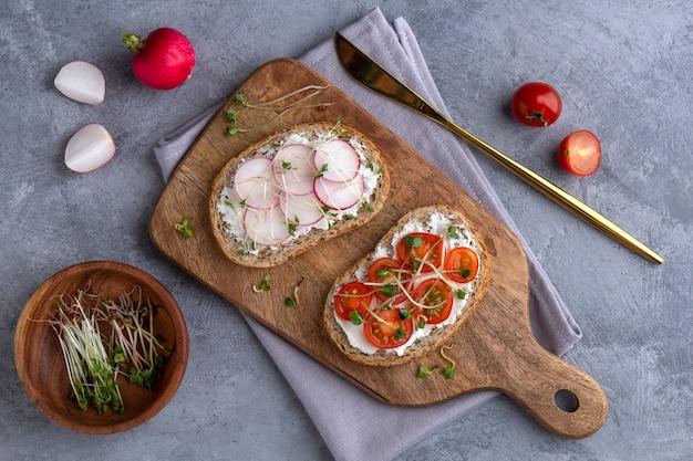 Плоское блюдо с бутербродами с овощами и микрогринами на серой поверхности