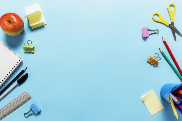 Плоская планировка с концепцией школы, образования или рабочего стола с различными школьными принадлежностями, ручками, карандашом, блокнотом, скрепками, яблоком, линейкой, ножницами, бумажной наклейкой на синей поверхности