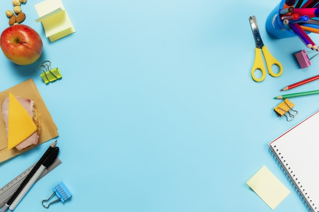 Плоская планировка с концепцией школы, работы или творчества с различными школьными принадлежностями, ручками, карандашом, блокнотом, скрепками, яблоком, орехами, бутербродом, линейкой, ножницами, бумажной наклейкой на синей поверхности
