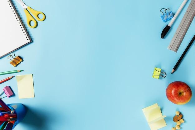 Плоская планировка с концепцией обучения, работы или образования с различными школьными принадлежностями, ручками, карандашом, блокнотом, скрепками, яблоком, орехами, линейкой, ножницами, бумажной наклейкой на синей поверхности