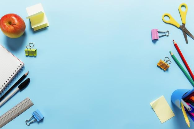 Плоская планировка с концепцией обучения, работы или образования с различными школьными принадлежностями, ручками, карандашом, блокнотом, скрепками, яблоком, линейкой, ножницами, бумажной наклейкой на синей поверхности