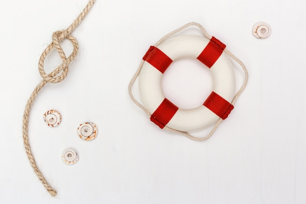 Flat lay with sea rope knot and lifebuoy on white background. copy space.