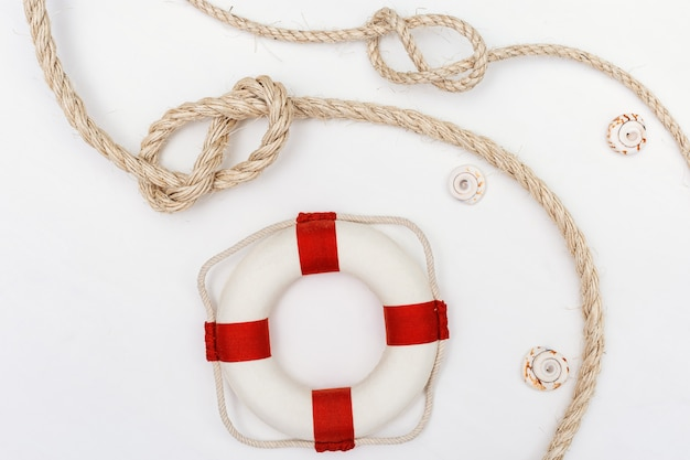 Flat lay with sea rope knot and lifebuoy.