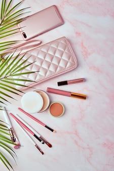 Плоская планировка с набором декоративной косметики, инструментов для макияжа и женских аксессуаров на розовом мраморе