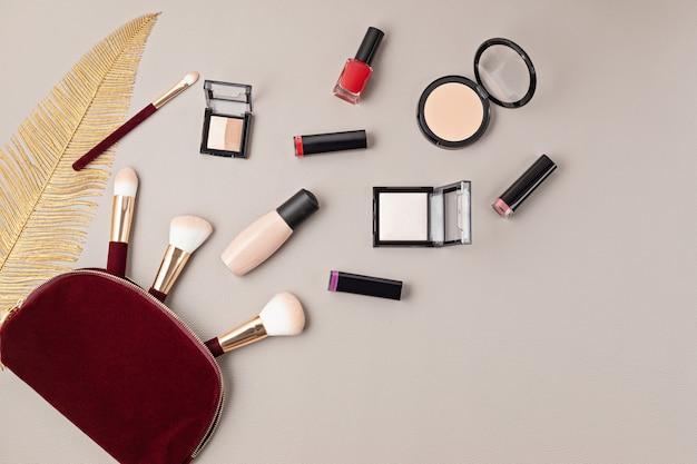 コピースペースのある灰色の壁の上に、プロの装飾化粧品、化粧道具、女性用アクセサリーのセットを置いたフラットレイ。美容ブログ、ファッション、パーティー、ショッピングのコンセプト。上面図