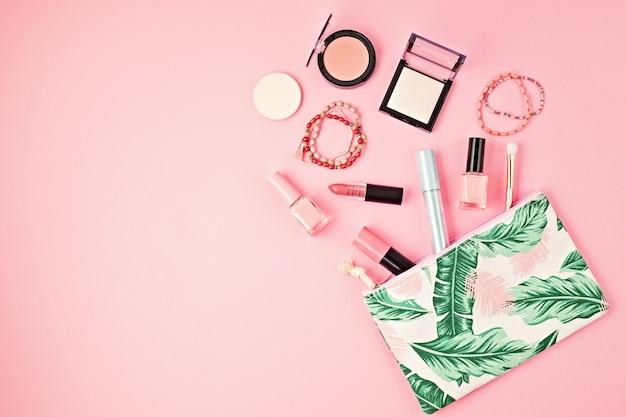 コピースペースのあるピンクの壁に、プロの装飾化粧品、化粧道具、女性の春、夏のアクセサリーのセットを備えたフラットレイ。美容ブログ、ファッション、パーティー、ショッピングのコンセプト。上面図