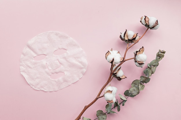 Flat lay with sheet facial mask and flowers on pink background