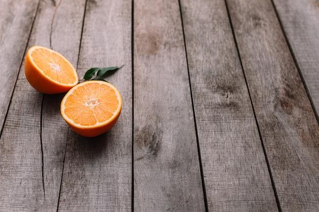灰色の木製の背景に新鮮で熟したオレンジ色の果実の半分をスライスしたフラットレイ。オレンジ果肉と緑の葉