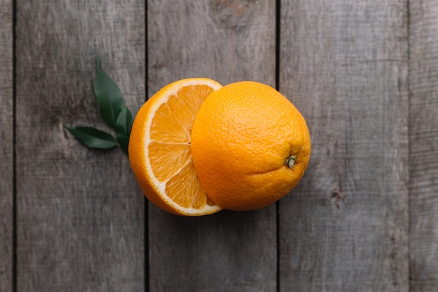 Плоские лежал с нарезанными половинками свежих и спелых апельсиновых фруктов на сером деревянном фоне