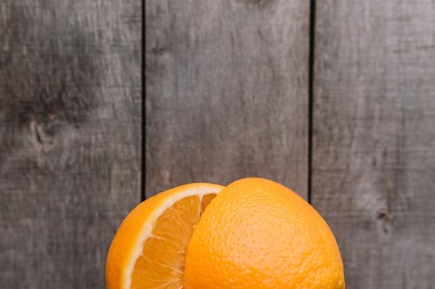 Плоская планировка с нарезанными половинками спелых апельсиновых фруктов со свежей мякотью на сером деревянном фоне