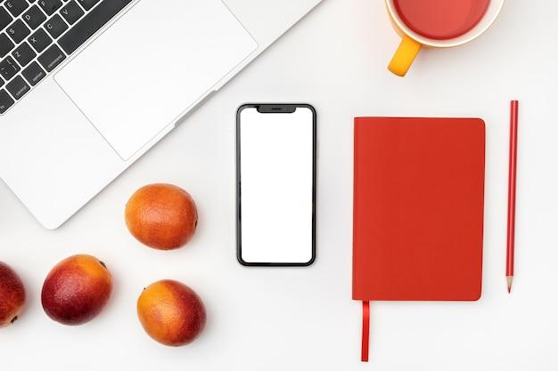 フラットは、スマートフォンの空白の画面、ノートパソコン、メモ帳、お茶で置く