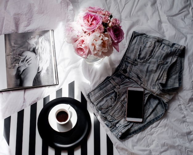 Flat lay with smartphone, bouquet of roses, coffee and magazine