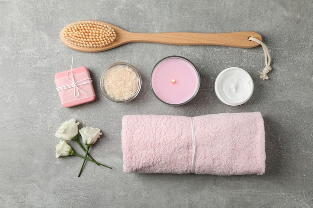 Flat lay with spa supplies on grey background, space for text