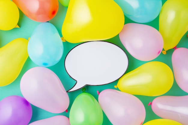 Flat lay with speech bubble and colorful balloons. birthday, party, celebration concept.