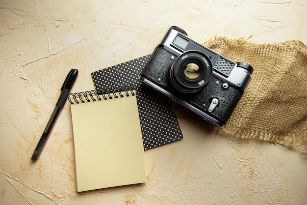 テクスチャードベージュの背景にスパイラルメモ帳キーボードペンと古いカメラでフラットレイ