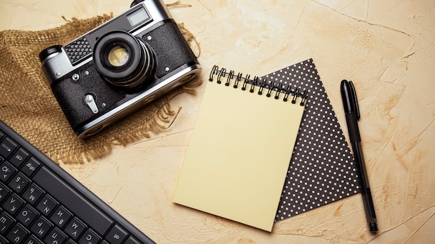 Flat lay with spiral notepad keyboard pen and old camera on textured beige background
