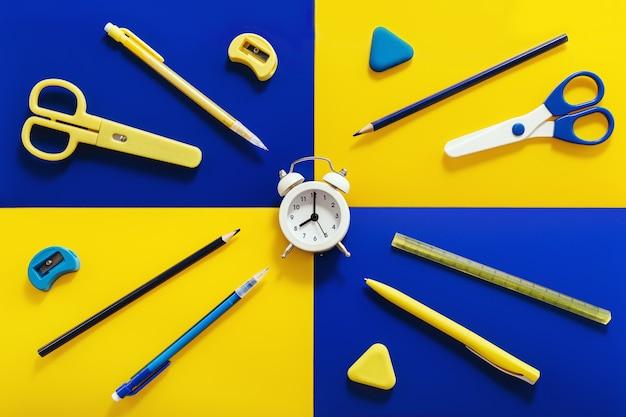 Плоская планировка с канцелярскими принадлежностями и школьными принадлежностями ярко-желтого и синего цветов Premium Фотографии
