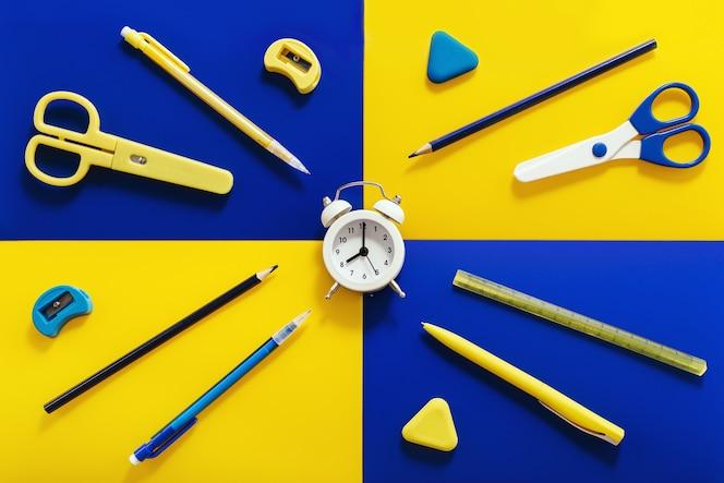 밝은 노란색과 파란색 색상의 문구 및 학교 용품이있는 평면 배치